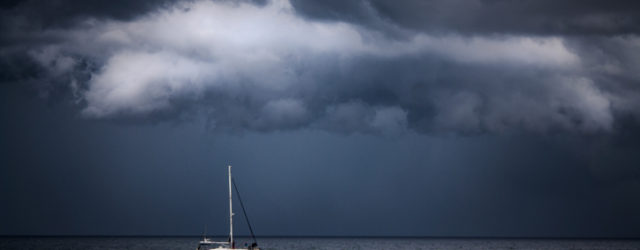 Boat sails under stormy clouds